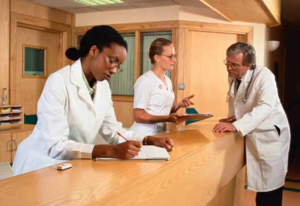 Three people in white lab coats working
