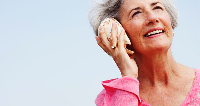 older woman holding a shell up to her ear