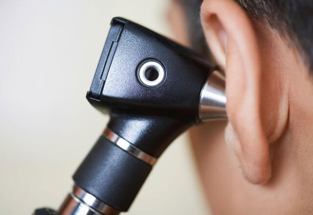 An otoscope being used to exam a patient's ear