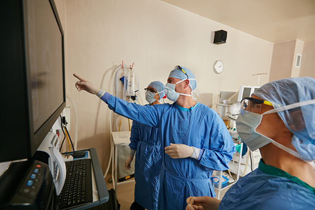 Three members of surgical team reviewing a computer screen in operating room.