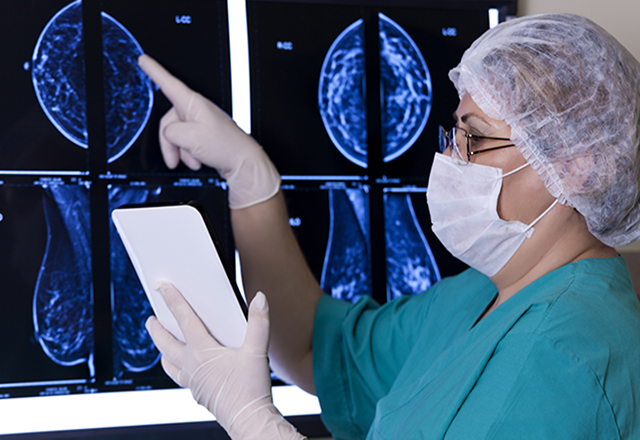 Female doctor reviewing mammogram renderings