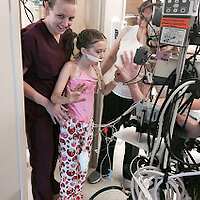 Therapists helping a child walk in a pediatric ICU