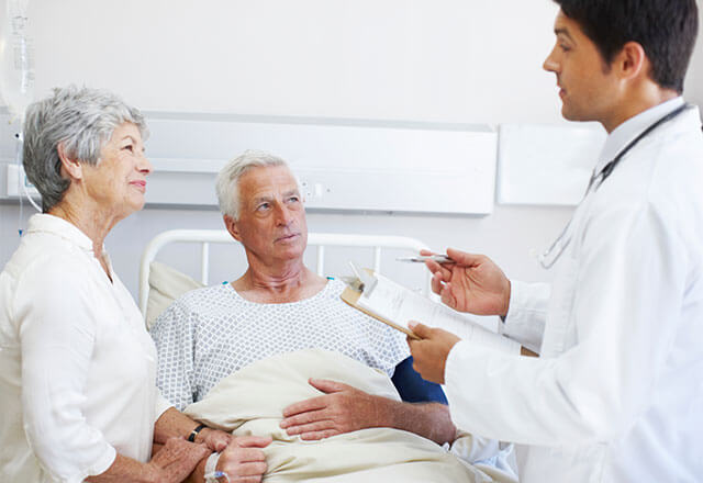 doctor talking to elderly patient and wife