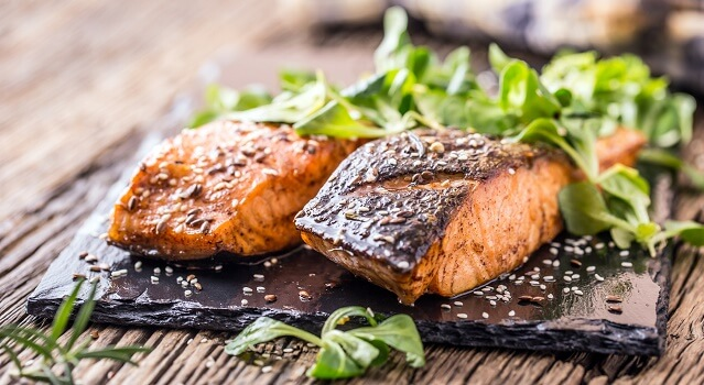 Two fillets of grilled salmon with arugula on gray slate