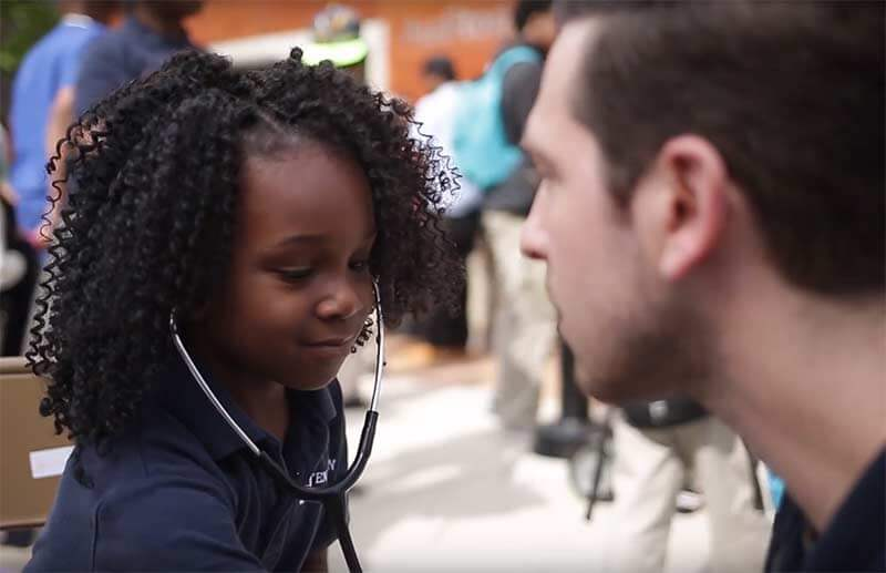 Young student listening to a doctor's heartbeat.