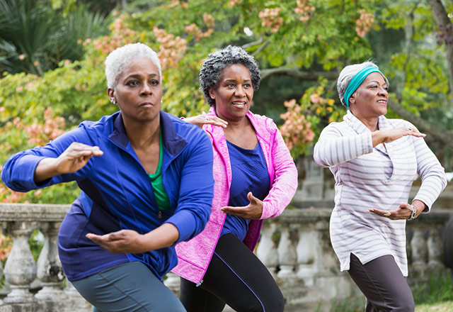 Three women enjoying Tai Chi class.