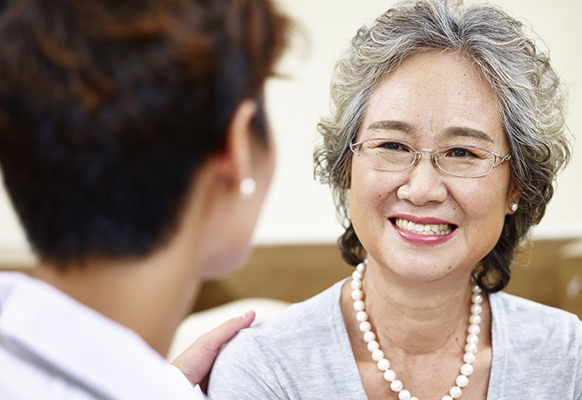 Woman smiling while talking with a doctor.