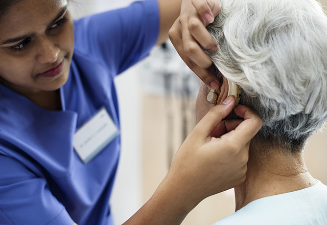 physician applying hearing aid to senior patient