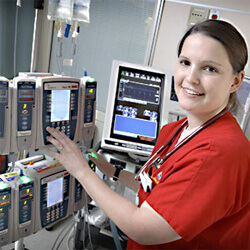 nurse in red scrubs in front of monitors