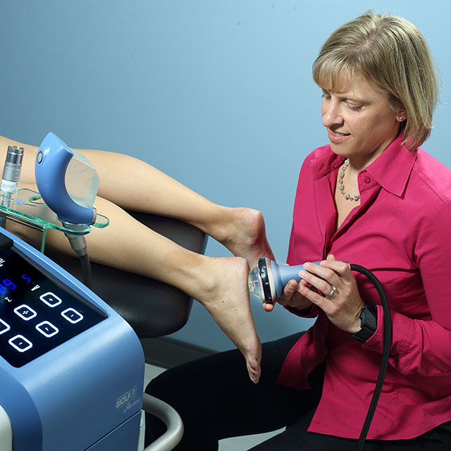 A physical therapist using the myofascial acoustic compression therapy machine on a patient's foot
