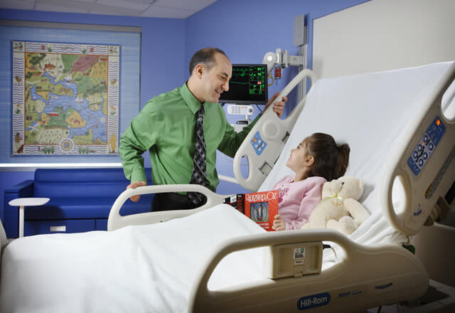 A pediatric specialist talks to a child lying in a bed.