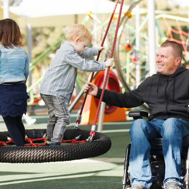 A man in a wheelchair playing with children