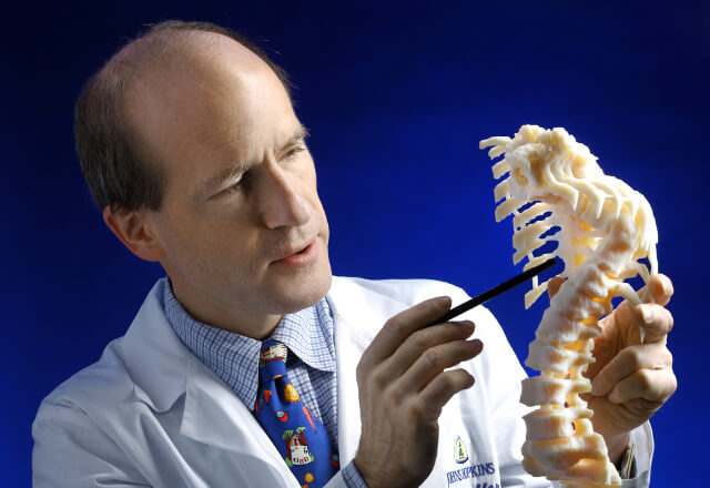 Dr. Paul Sponseller with a model of a deformed spine