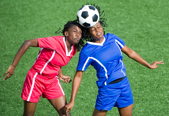 Two female soccer players collide while trying to head a ball.