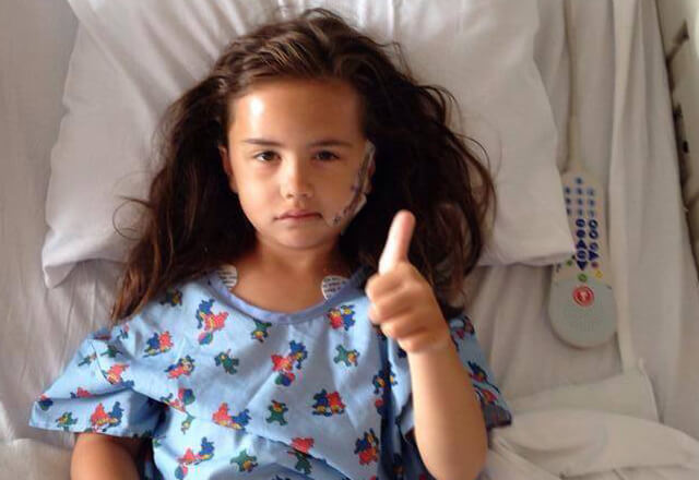 Demi sits in her hospital bed and gives a thumbs up