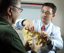 "Adam Levin consults with patient Julian Sparrow. ""Having a team that is used to working on these particular cases is vital,"" he says. Below, a right acetabular fracture and multiple hip fractures are repaired with staged proximal femur resections and reco"
