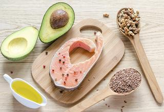Fish, avocado, nuts and olive oil arranged on a wooden cutting board