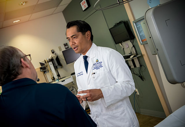 Dr. Phuoc Tran speaking with a patient.