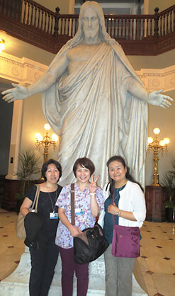 Three visiting nurses in front of statue.