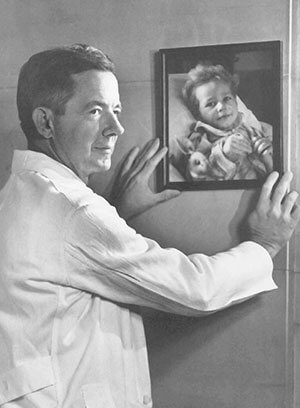 Dr. Blalock with a portrait of a blue-baby patient on the wall
