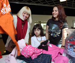 At a recent Shop 'Til You Drop event sponsored by Healthy Families, Judy Templeton, left, and Raquel Arias help Raquel's daughter, Klarissa, select outfits from piles of donated clothes. Arias' metal artwork was also on display.