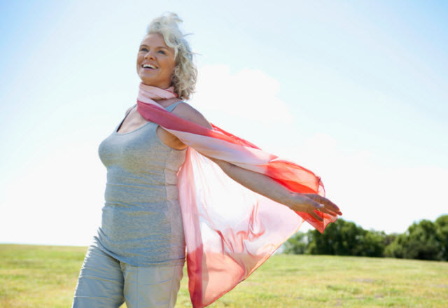 woman smiling with scarf  blowing in the wind
