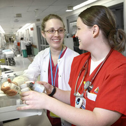two nurses holding prescription bottles