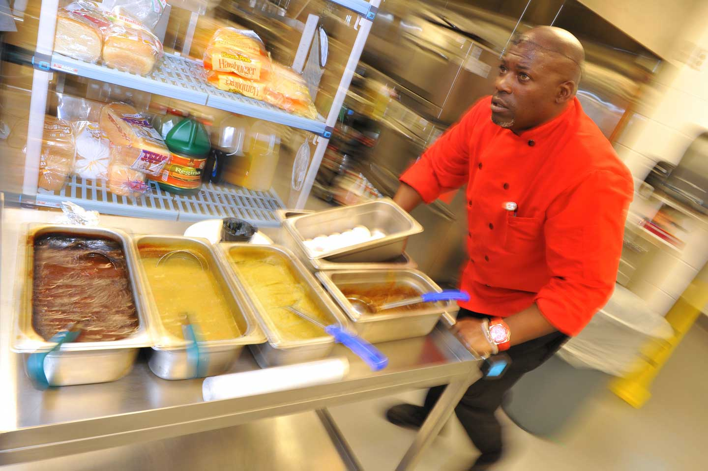 In the hospital's new kitchen, cook Terence Beatty delivers a cart filled with the fixings      for meals being made for arriving patients.