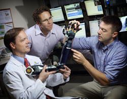 Neurologist Nathan Crone (left) is working with colleagues from the Johns Hopkins Applied Physics Laboratory, including Matthew Johannes (center) and Brock Wester (right), to develop a prosthetic arm using electrical signals from epilepsy patients' brains