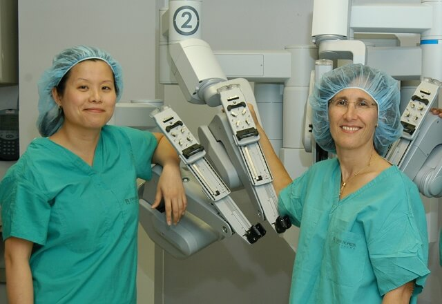 Dr Handa and Dr Chen in scrubs with surgical robot