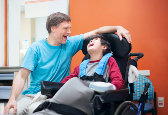 boy in wheelchair laughing with his father