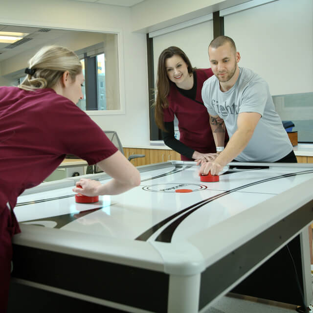 A patient playing air hockey with occupational therapists