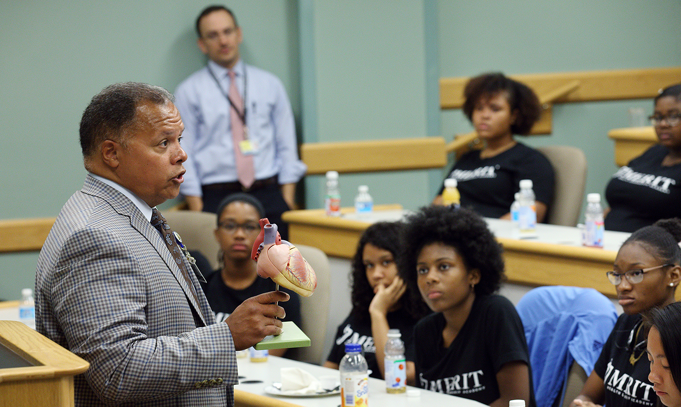 Robert Higgins, holding up a plastic model of the human heart, speaks to a classroom of high school students.