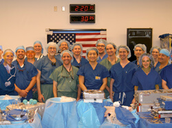 A TRIUMPH OF TEAMWORK: Surgeons who participated in the double arm transplant gather in the operating room shortly after the historic surgery. W.P. Andrew Lee, center, director of the team, is flanked by surgeons from Johns Hopkins, the Curtis National Ha