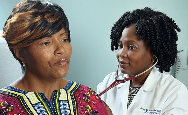 Dr. Falade-Nwulia meeting with a patient.