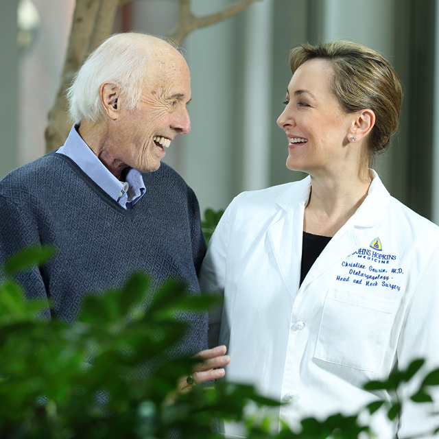 Photograph of patient Al Friendly Jr. smiling a laughing with Dr. Christine Gourin. They are looking at each other joyfully.