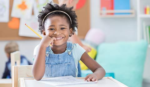 Kindergarten student smiling at her desk.