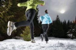 two women running in the snow