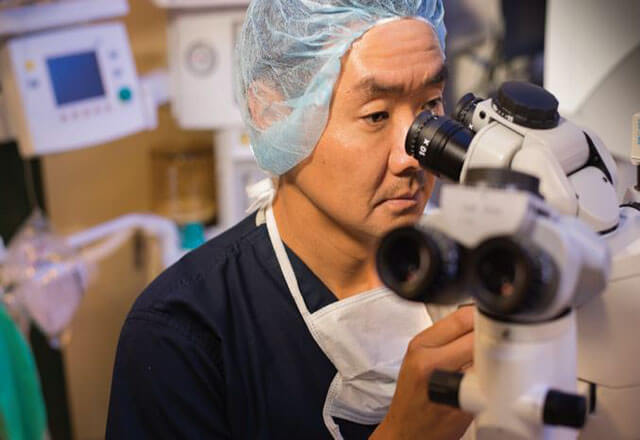 Dr. Jun looking through microscope