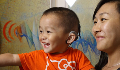 Young kid with  a cochlear implant smiles with his mother