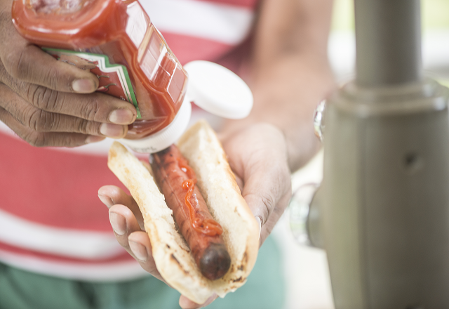 A person puts ketchup on their hotdog.