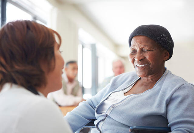 patient in a chair smiling at a caregiver