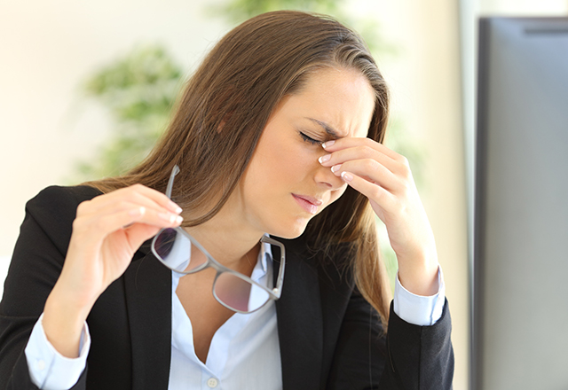 Woman with a headache at the office