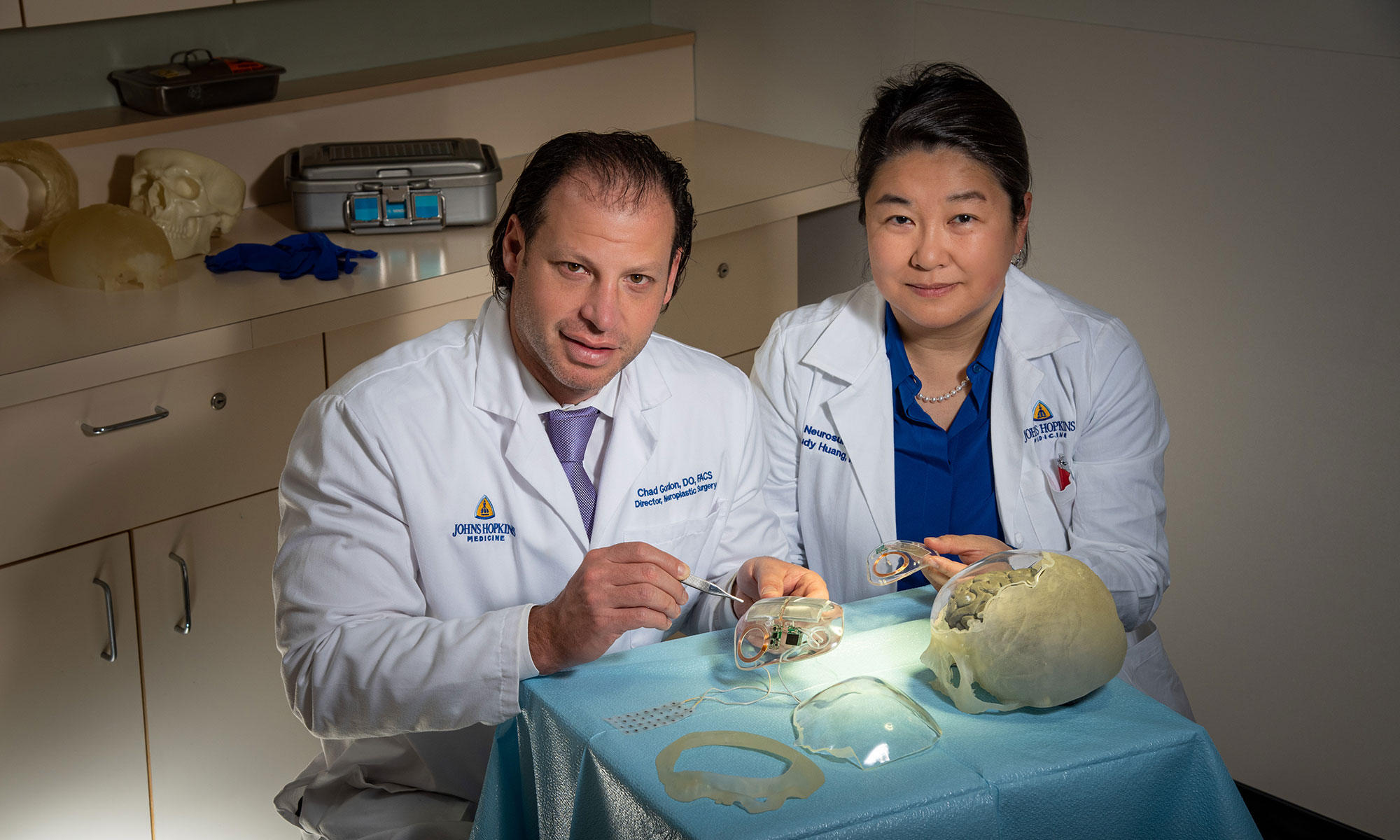 Craniofacial plastic surgeon Chad Gordon and neurosurgeon Judy Huang, wearing lab coats, hold neuroplastic devices in their hands that consist of clear plastic implants with electric parts embedded in them.