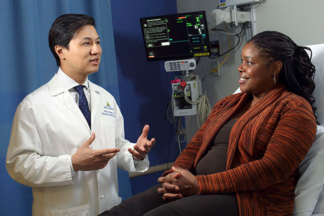 Dr. Hong speaking with a patient