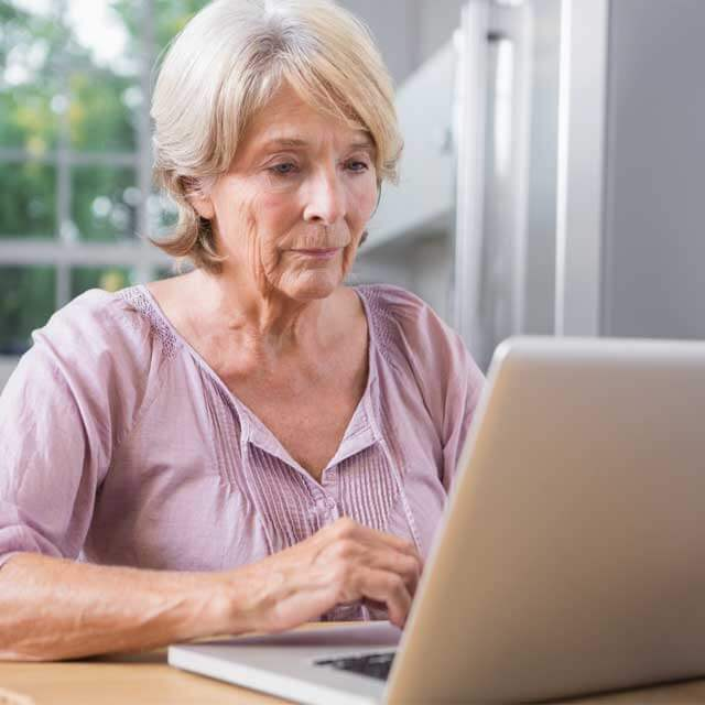 elder woman researching on a laptop