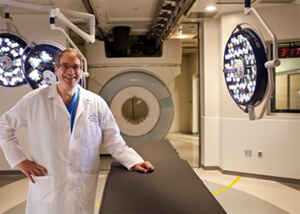 photo of Dr. Henry Brem standing in front of the intraoperative MRI machine