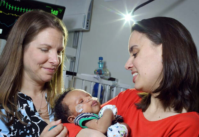 nurse with a mother and baby in NICU