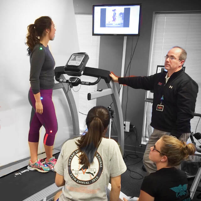 A team of physical therapists guiding a patient on the gait analysis treadmill