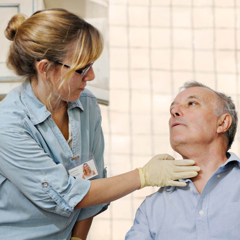 Doctor examining a male patient's throat